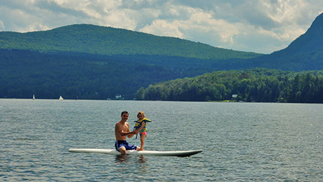 Father and daughter paddleboarding at Green Acres Cabins beach